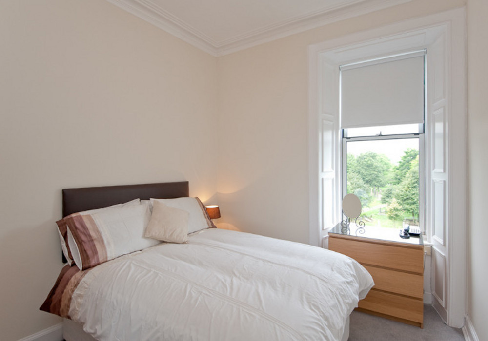One of the lower floor bedrooms - Featuring a fixed double bed and benefiting from views out across the park.