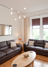 The spacious living room - This living room, the first of two in this fantastic apartment, features three full size leather sofas, one of which becomes a sofa bed if required.