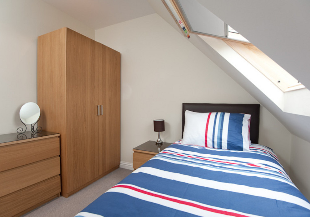 One of the upper floor bedrooms - Light and airy, featuring a velux window with views across the park. This bed features an optional pull-out bed allowing the room to be set-up as a single, double or twin (two singles) bedroom.